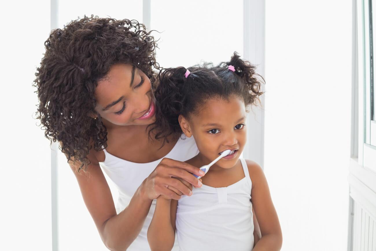 Mom helping daughter brush teeth before family dentistry visit