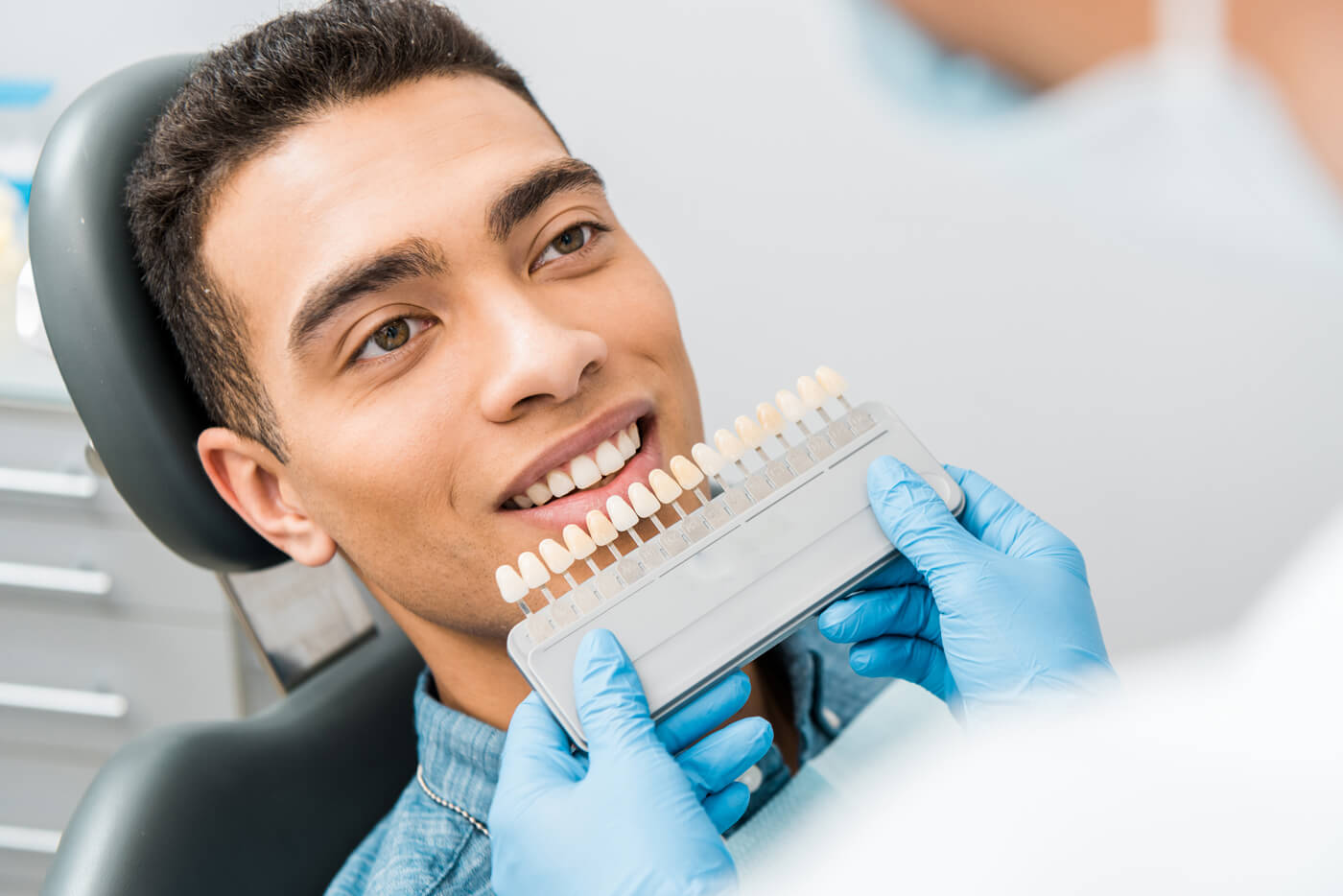 Dentist matching tooth color for veneers