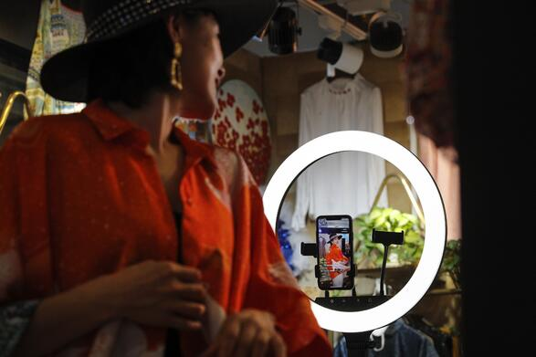 Woman presenting clothes in front of smartphone via Livestream shopping app. Source: www.scmp.com