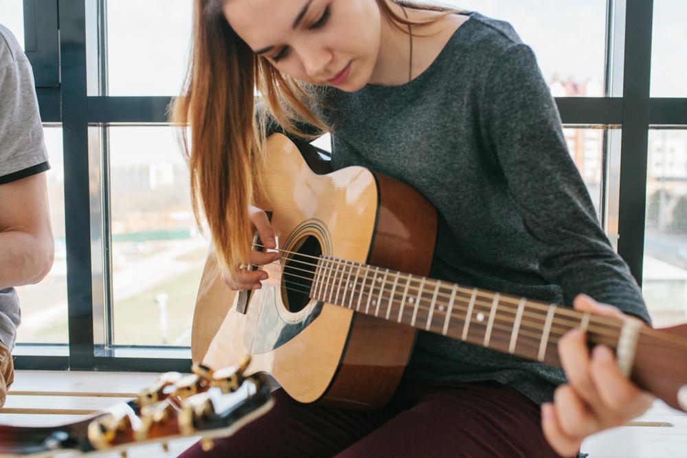 Mergina mokinasi groti gitara
