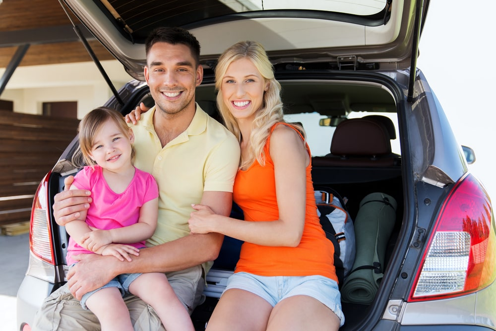 a family sitting in the back hatch