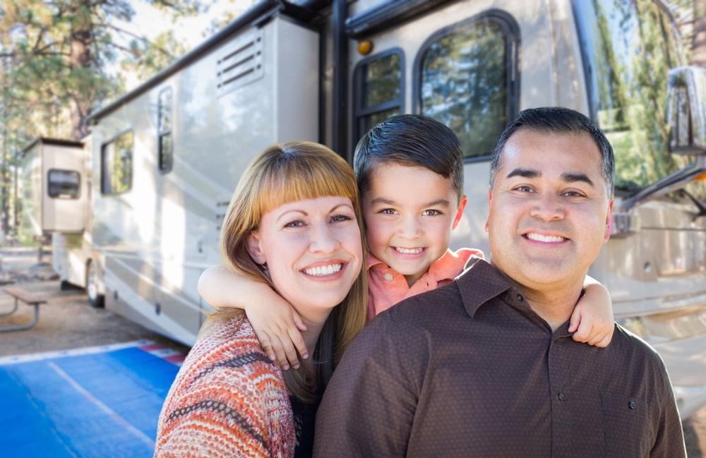 family outside their travel trailer