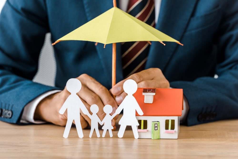 hands with paper cut family, house model and umbrella on wooden table