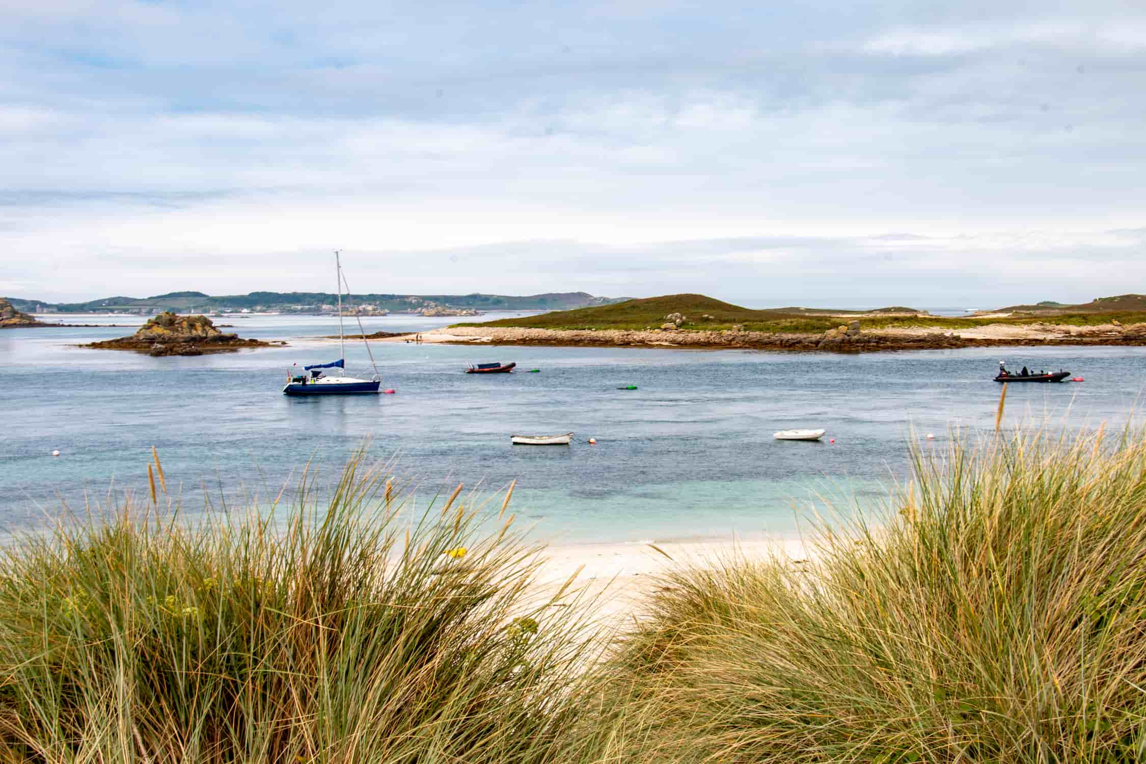 panoramic view of the isles of scilly from st martings in cornwall with boats mored and hugh town in the distance