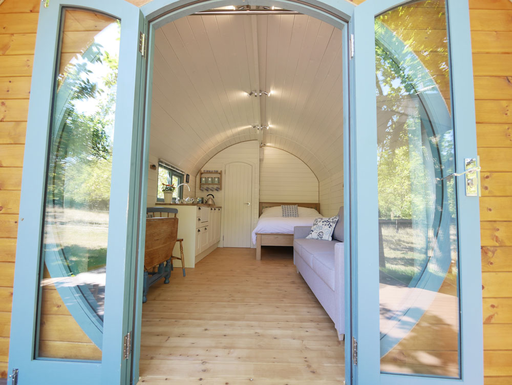 glamping pods on the isles of scilly cornwall interior with bed and round door