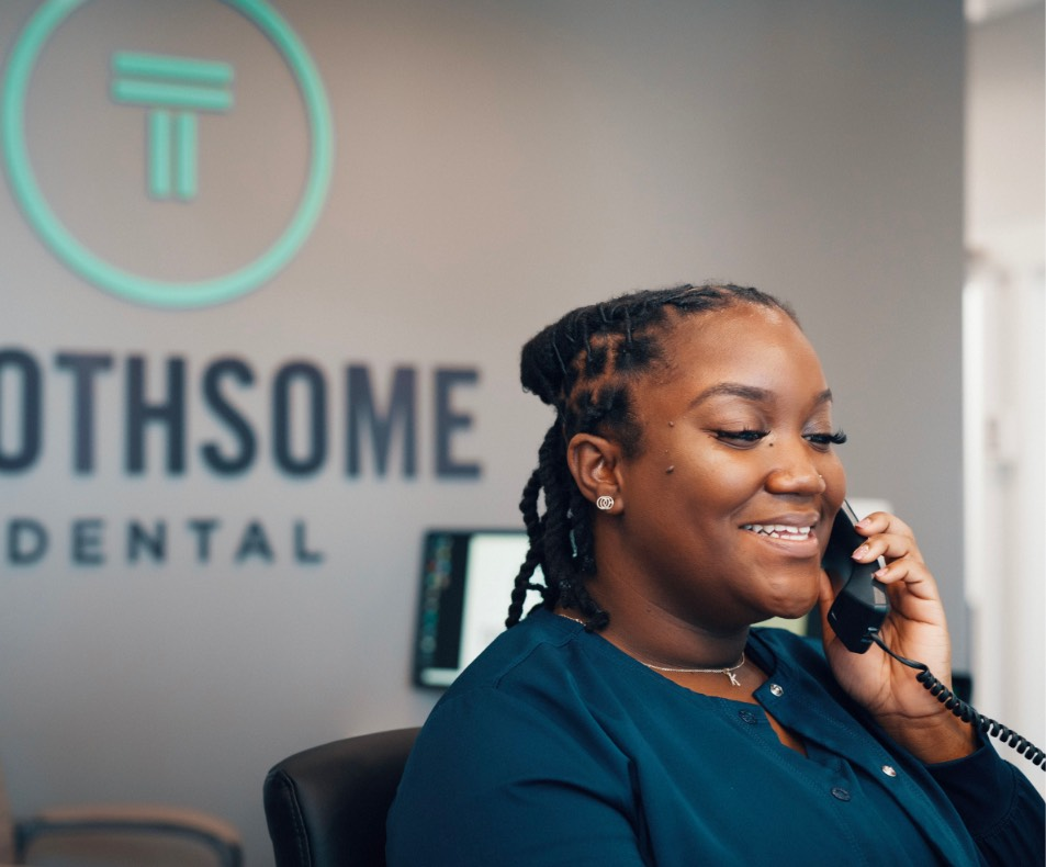 Photo of a Toothsome Dental team member on the phone with a patient