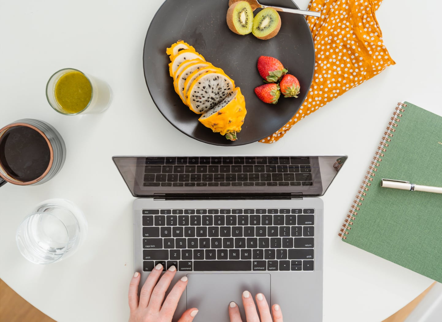 Hands on a laptop keyboard with a plate of fruit beside