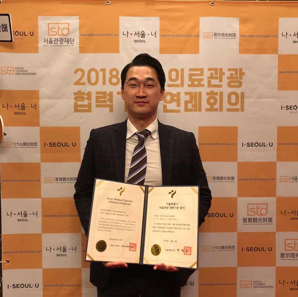 doctor lee ji yong holding certificate for medical tourism alliance from the korean government