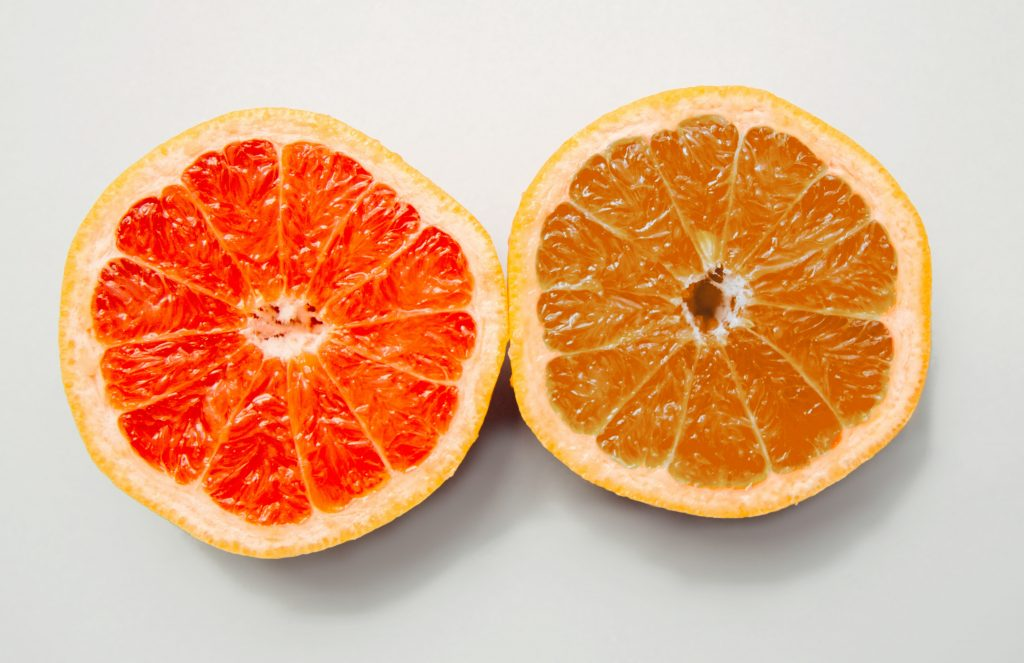 An orange and a grapefruit in a side-by-side comparison. They look the same on the outside but different colors on the inside.