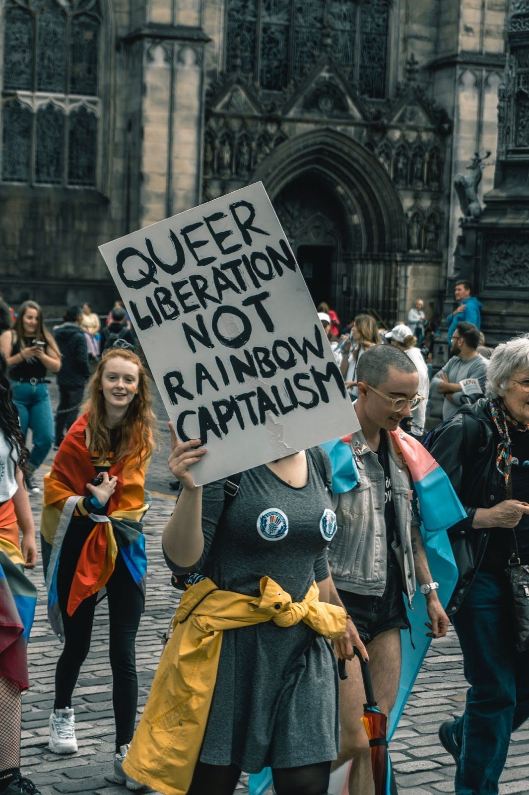 """Protestor holding a handmade sign that reads, """"Queer liberation, not rainbow capitalism""""."""