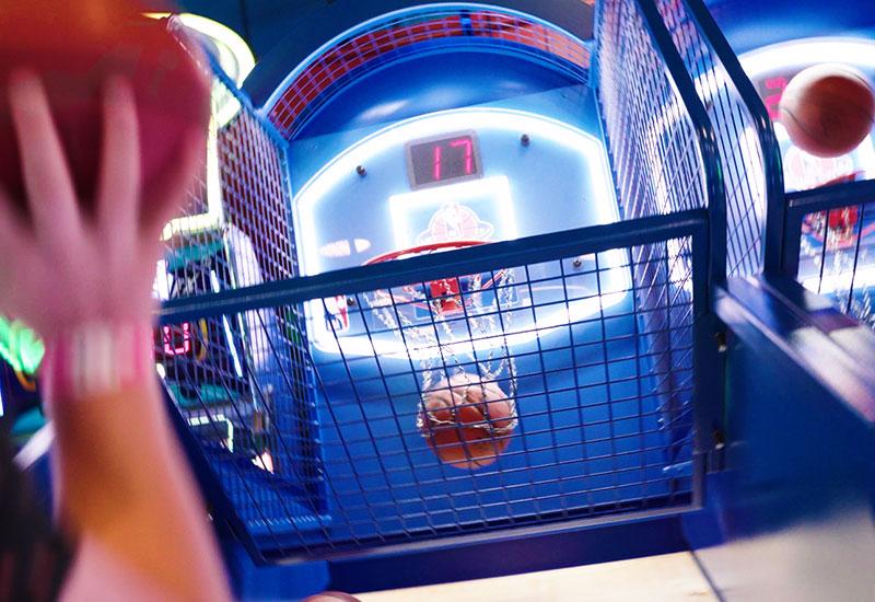 Family playing basketball at the arcade
