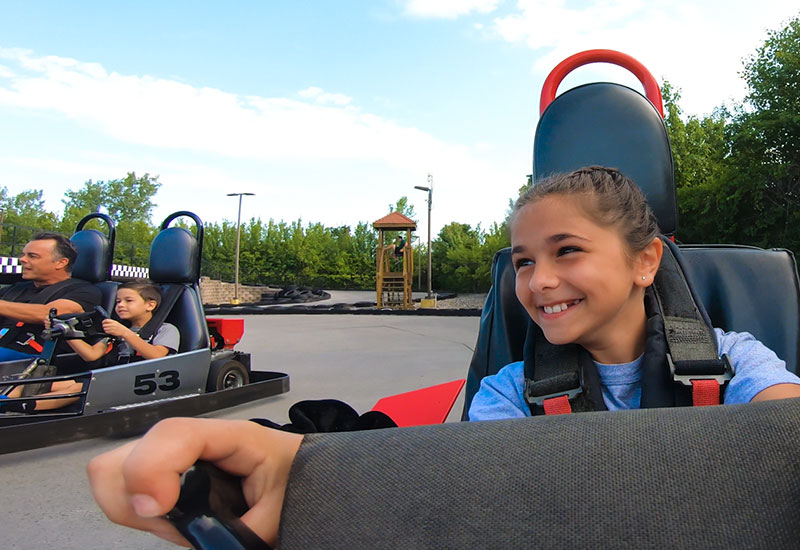 Girl driving a gokart with her family