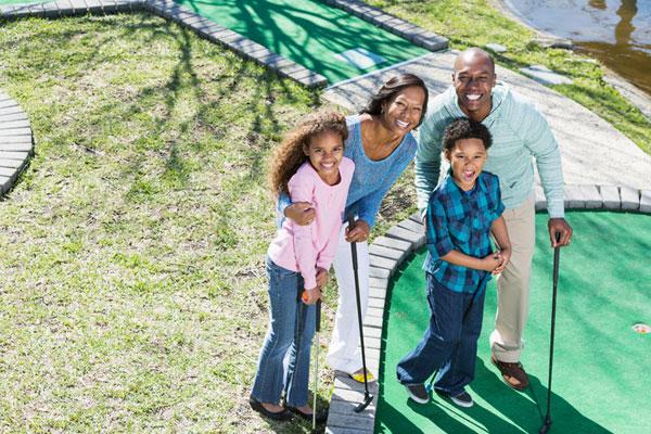 Family playing putt putt golf