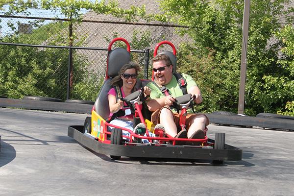 A couple driving go-karts in Henrietta