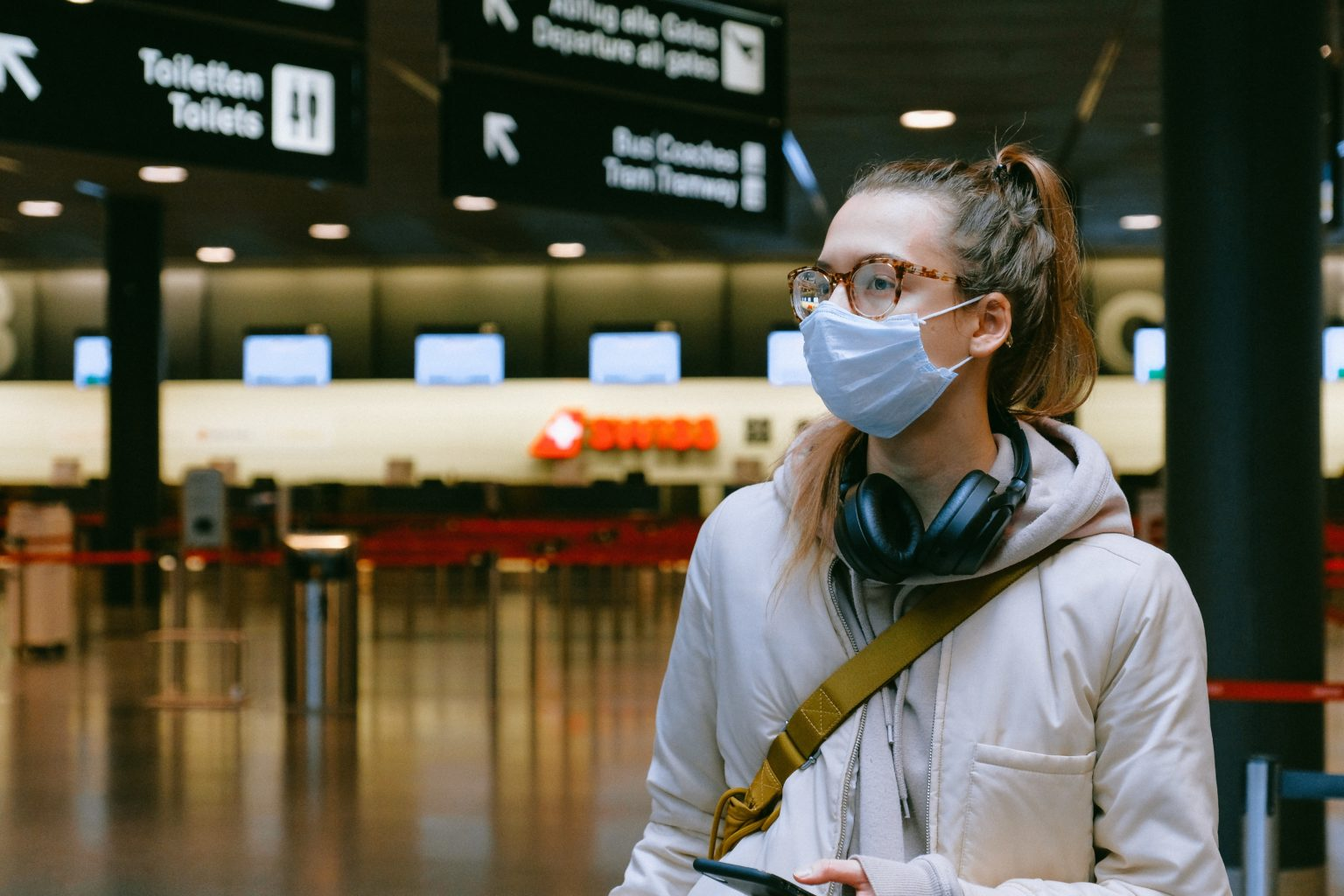Woman at an airport with a mask on.