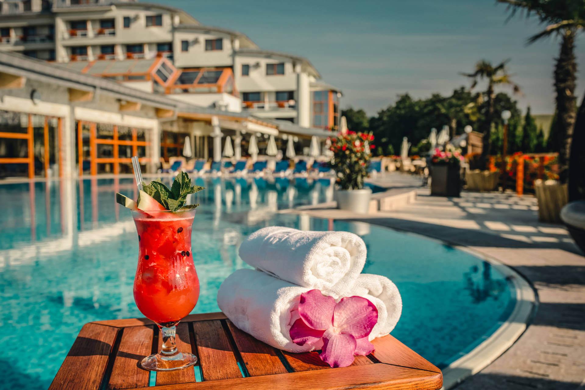 Vonkajší bazén v resorte Kaskady s letným drinkom, nápojom