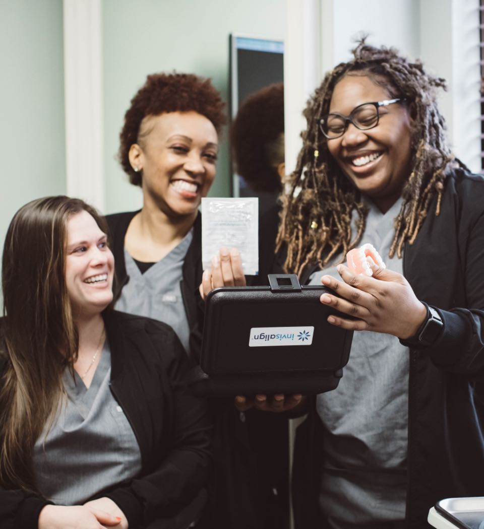 Photo of three Edgewood team members smiling holding up Invisalign products