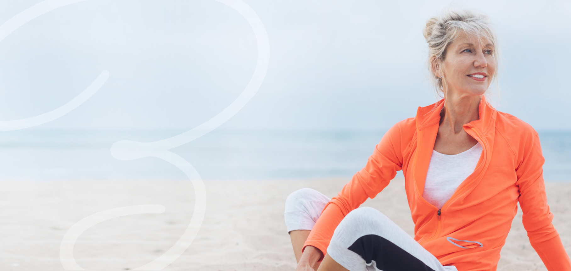 Attractive middle-age woman happy to be doing yoga at the beach.
