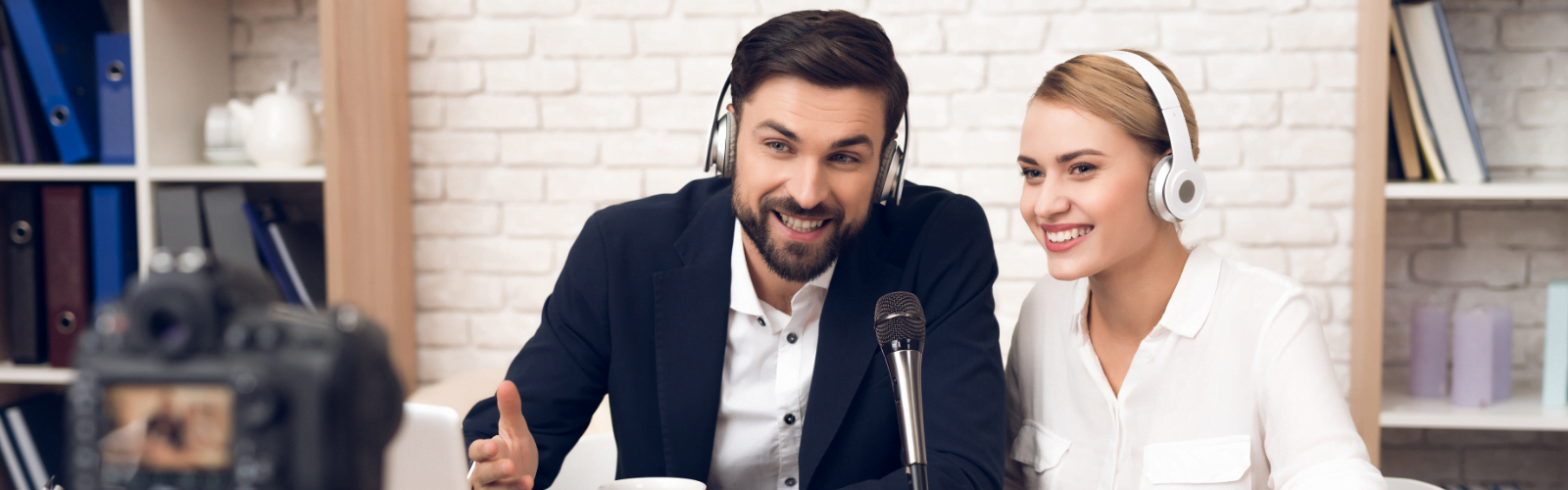 A man and a women podcasting and smiling