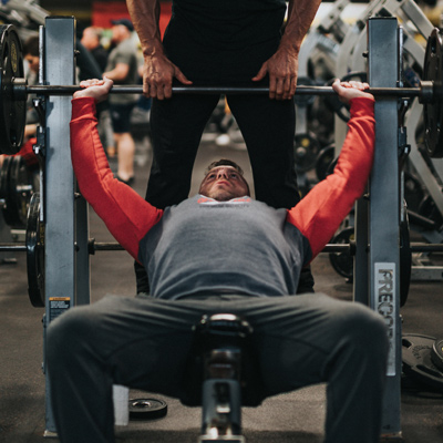 man working out on bench press with assistance of personal trainer