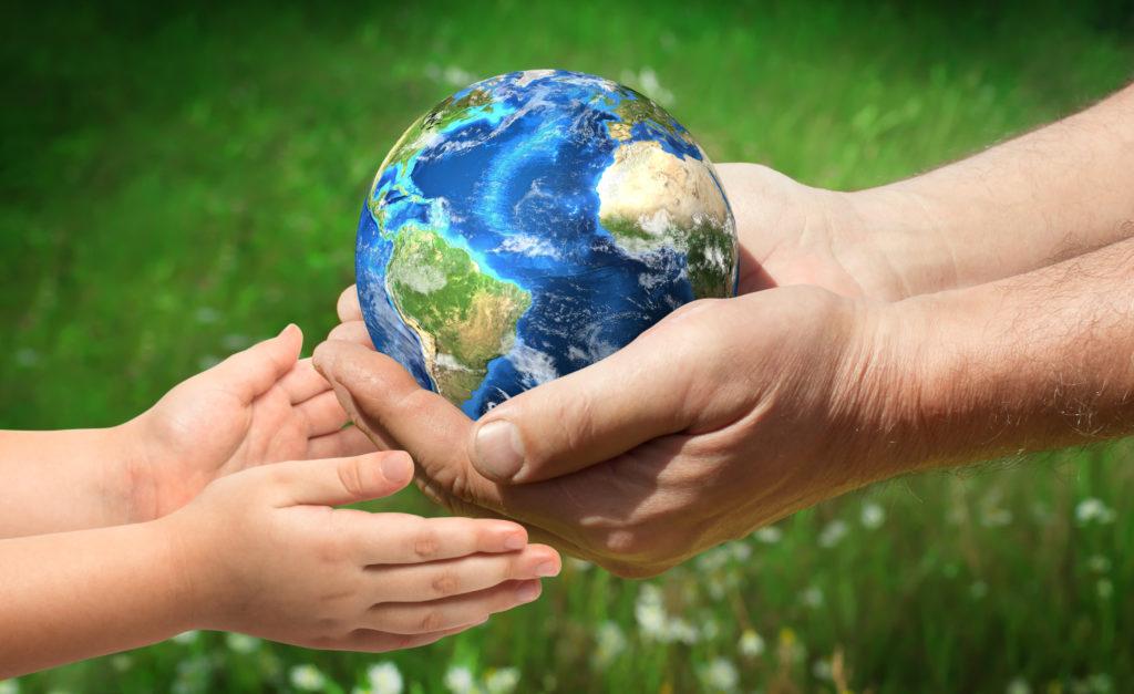 Мъж, подаващ планетата Земя в ръцете на дете, със съвет да рециклираме, за да я опазваме и в бъдеще