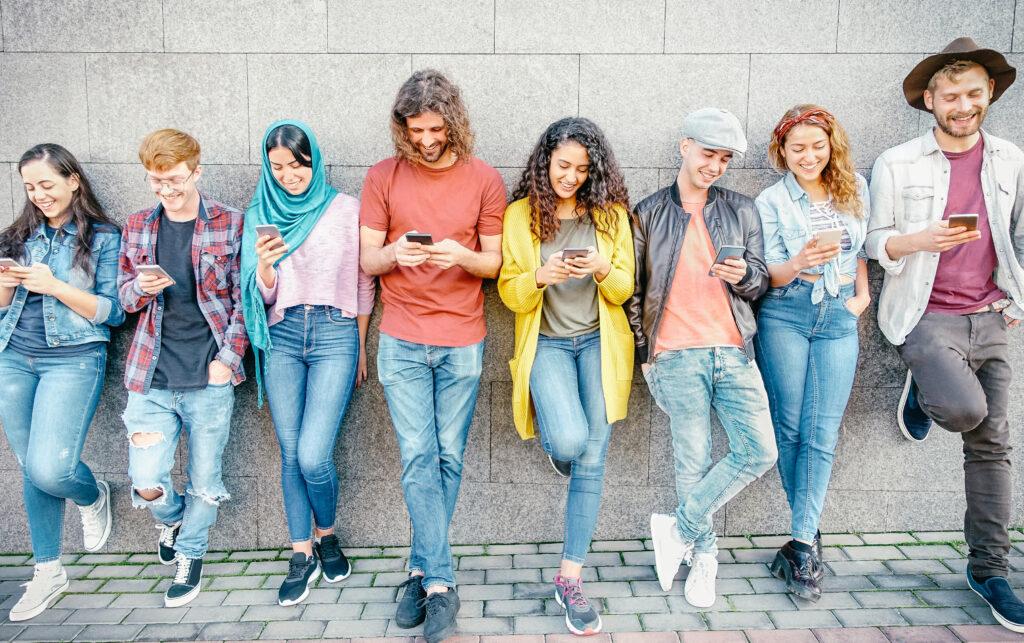 Младежи, погълнати от профилите си в различни социални мрежи, използващи своите смартфони