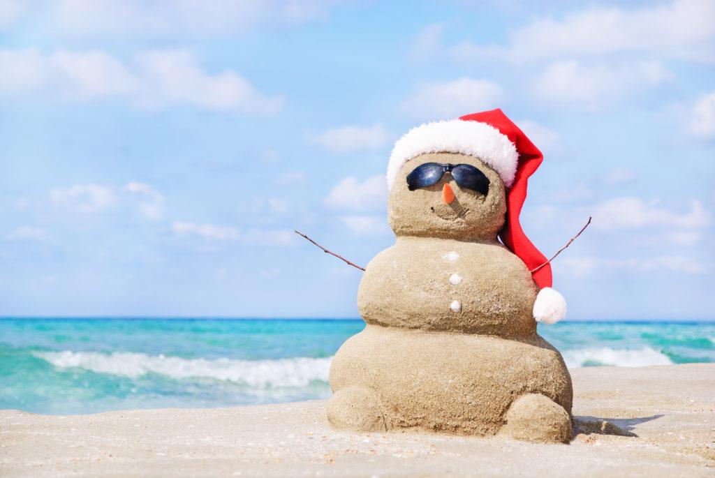 Снежен човек, направен от пясък, по време на летен отпускарски сезон