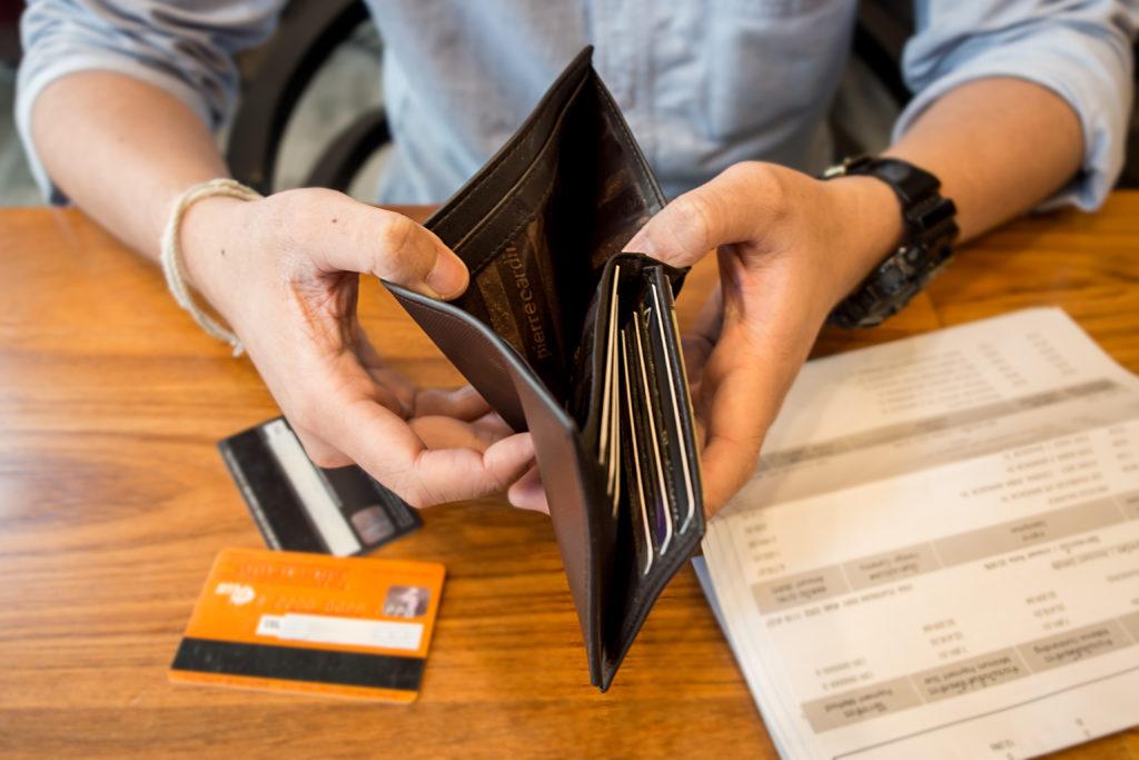 Човек с празен портфейл, нуждаещ се от теглене на лесни кредити, за да плати сметките си