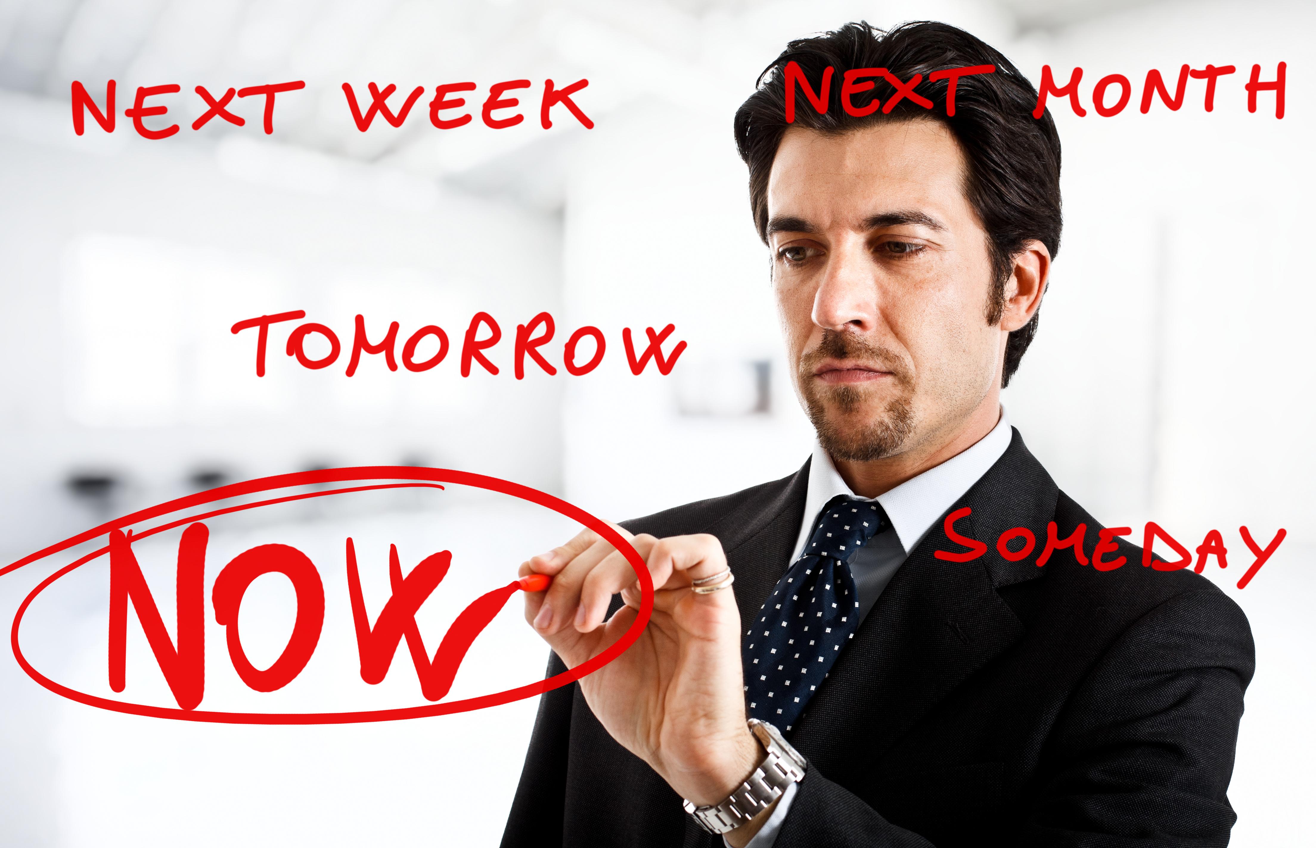 Бизнес мъж, който отбелязва, че трябва да се действа сега, а не да се чака до последния момент