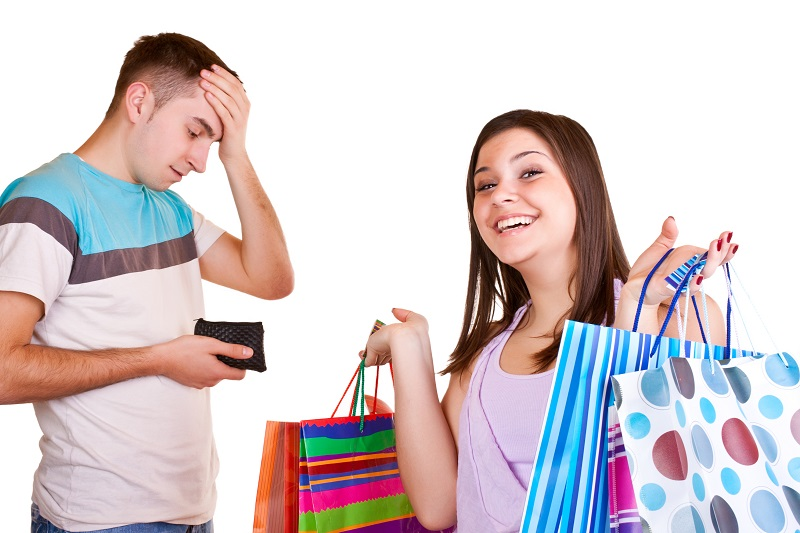young man standing with wallet while woman standing with bags