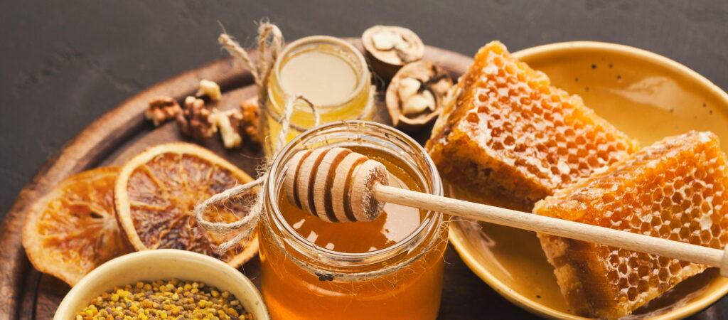 Бурканче с мед, пчелна пита, ядки и нарязан портокал