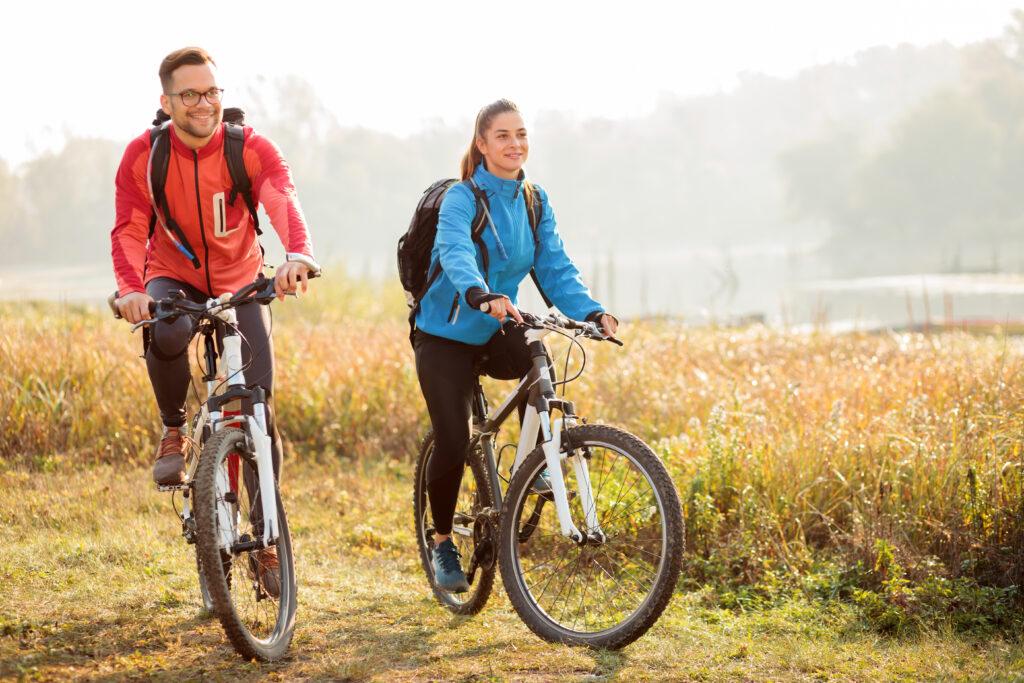 Каране на колело от двойка по изгрев слънце