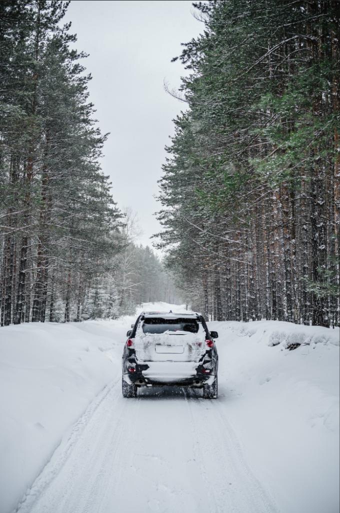 Автомобил, придвижващ се по затрупан със сняг път, при тежки зимни условия