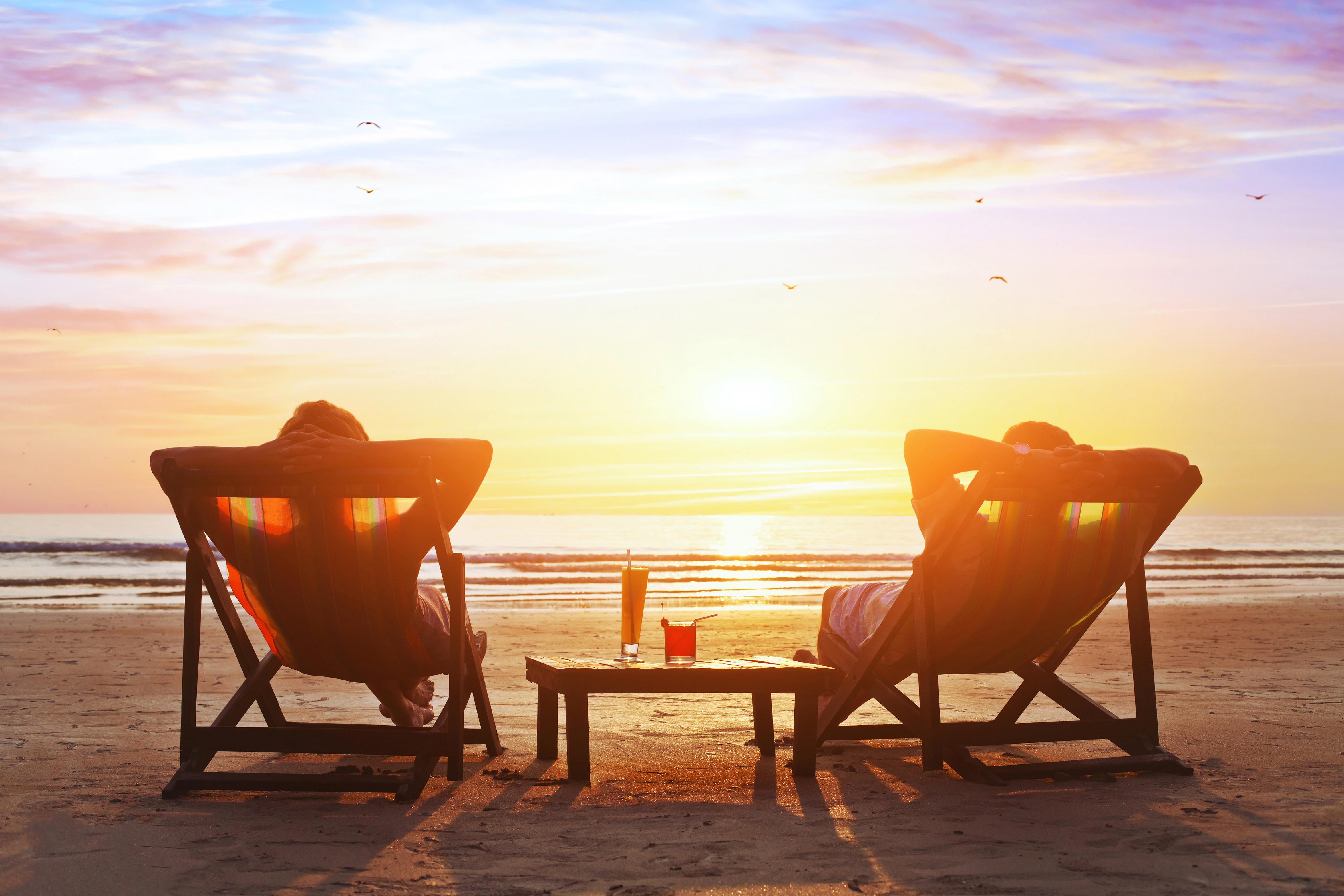 Мъж и жена се наслаждават на залеза по време на своята почивка на морето