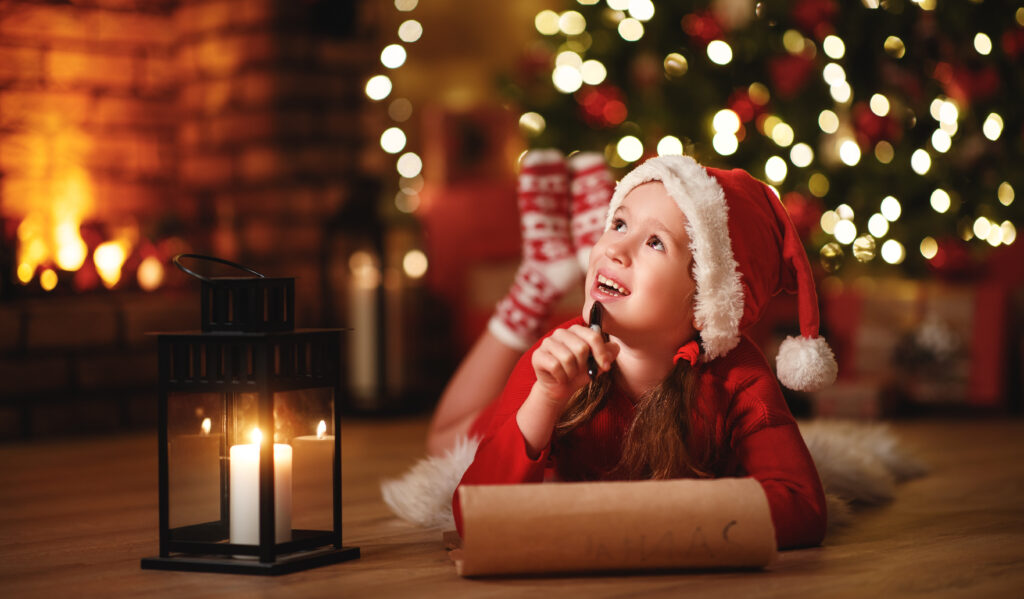 Момиченце, пишещо писмо до Дядо Коледа с желаните подаръци за Коледа