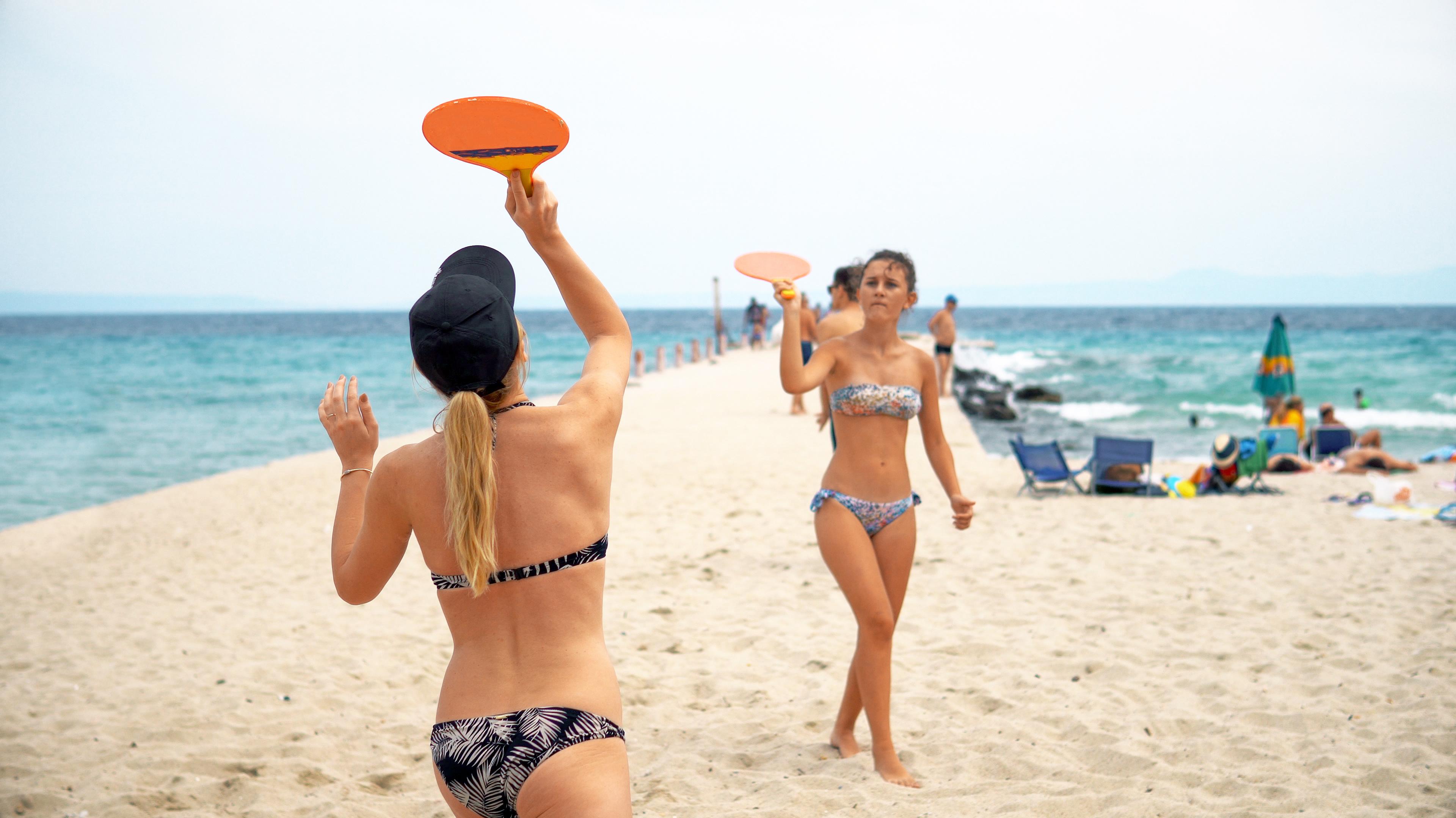 Супер забавление - момичета играят плажен тенис на брега на морето