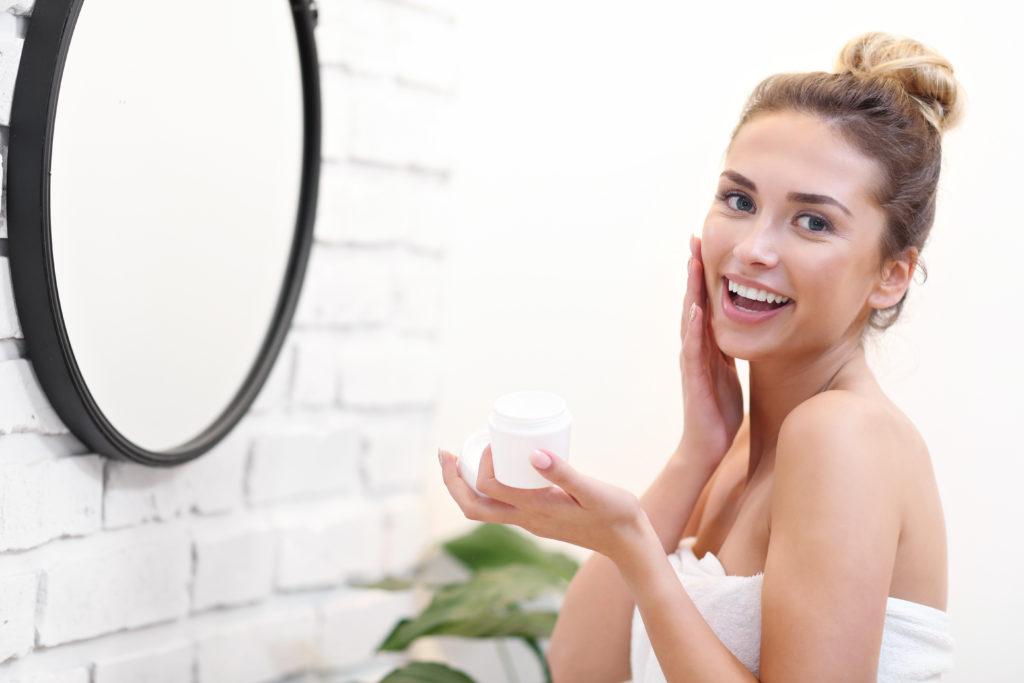 Красива млада жена, използваща трикове за красота за почистване на лицето си