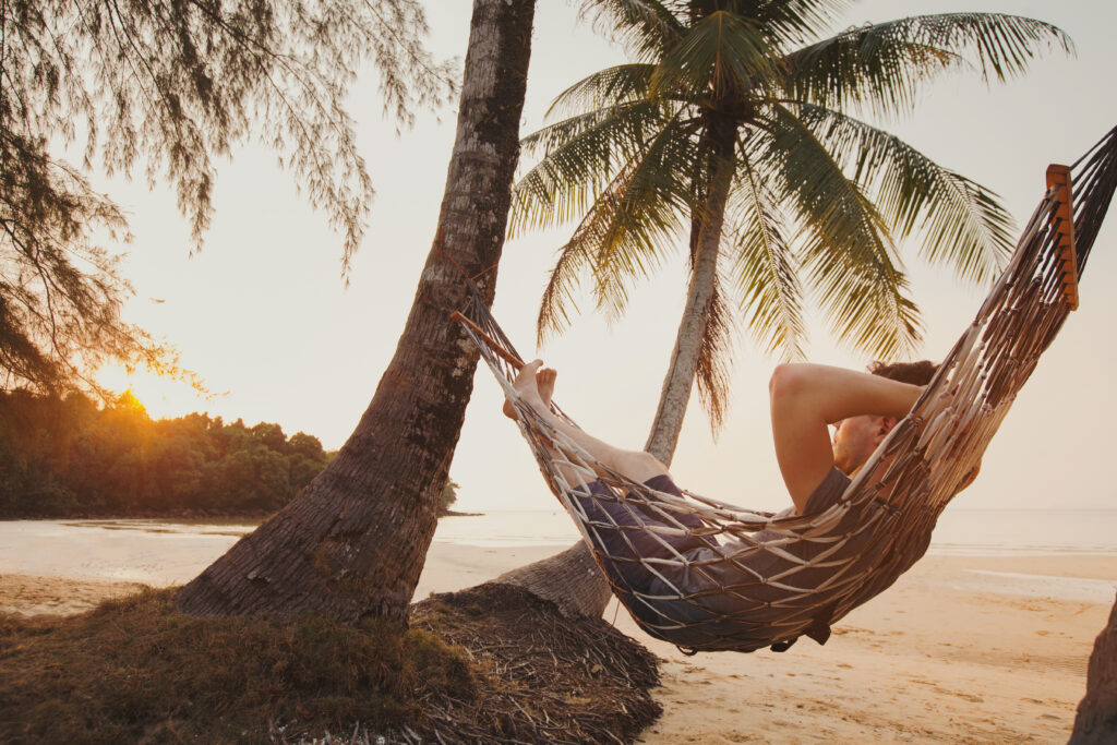 Мъж, лежащ на хамак на красив плаж през своето свободно време