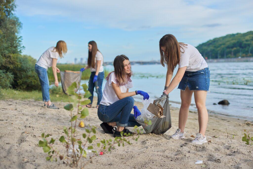 Момичета, почистващи брега на река от боклуци, с цел чиста природа