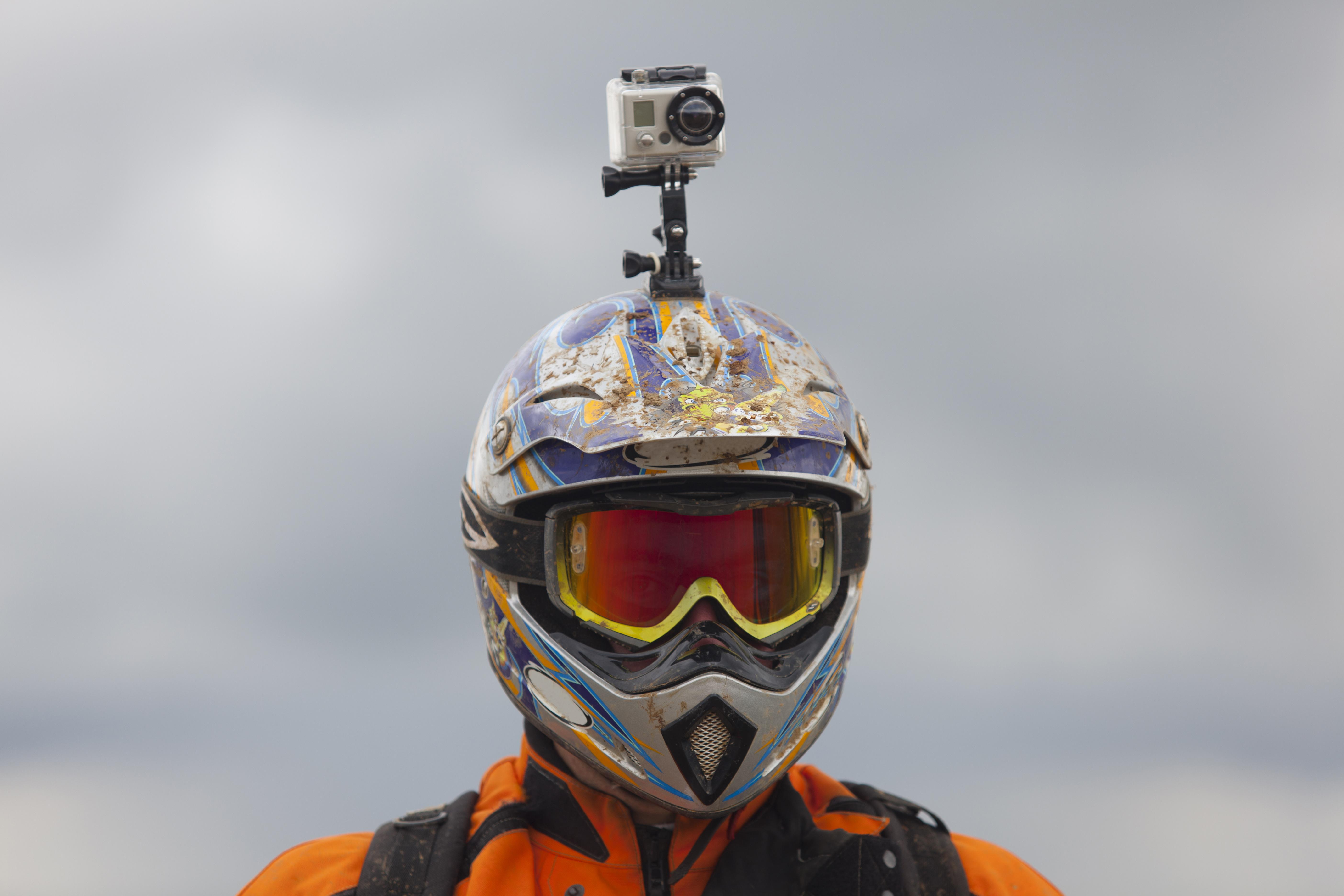 Модерни играчки - екшън камера, посавена на каската на човек, занимаващ се с мотокрос
