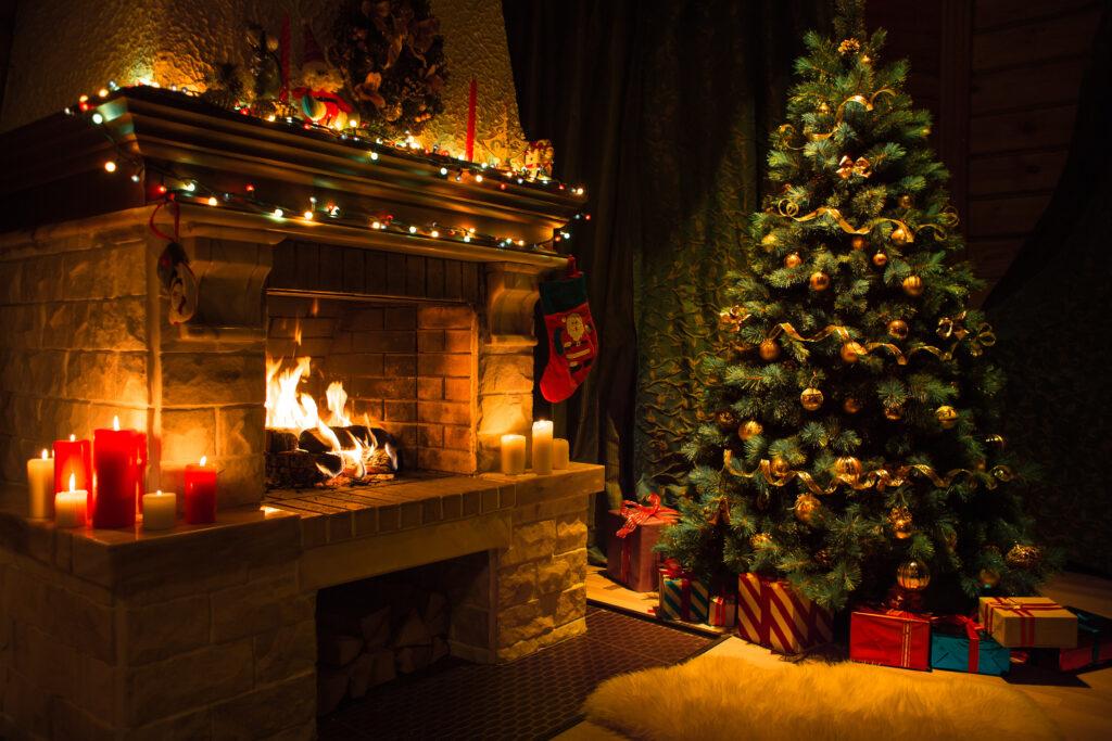 Горяща камина и елха с подаръци, предразполагаща към измисляне на оригинални пожелания за Коледа