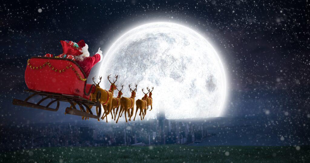 Дядо Коледа с шейната си, теглена от елените му, на фона на Луната
