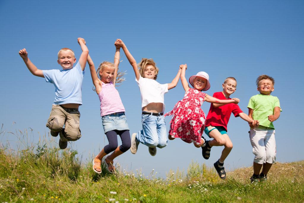 Щастлива група деца, хванати за ръце и подскачащи на поляна на Ден на детето