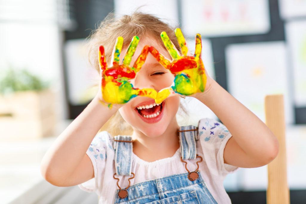 Момиченце, нацапало ръцете си с боички на Ден на детето