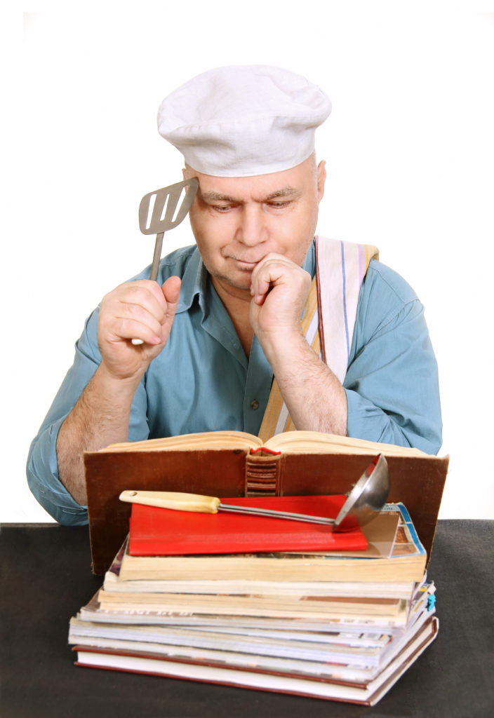 Мъж чете книга със съвети в кухнята, за да приготви хубава марината за месо