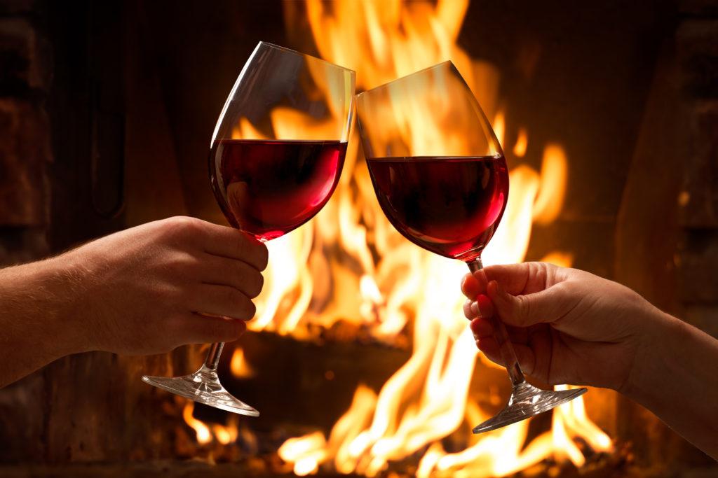 Чукване на чаши, пълни с вино, на Трифон Зарезан пред запалена камина