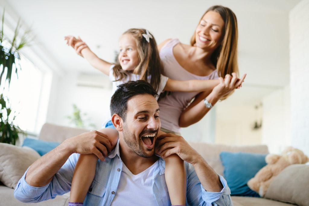 Семейство от мъж, жена и дъщеря им, които са щастливи заедно
