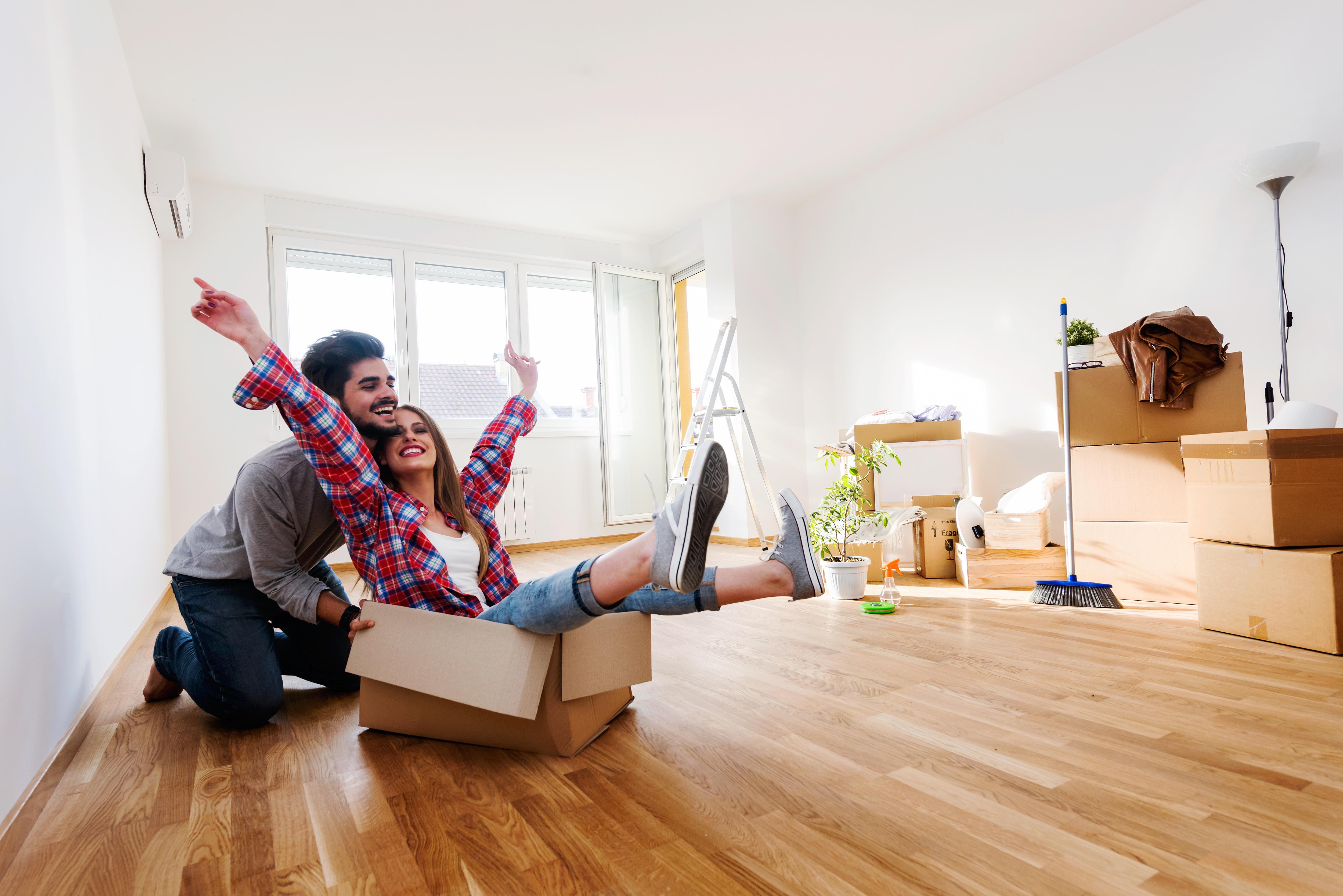 Щастлива двойка се забавлява в новия си апартамент
