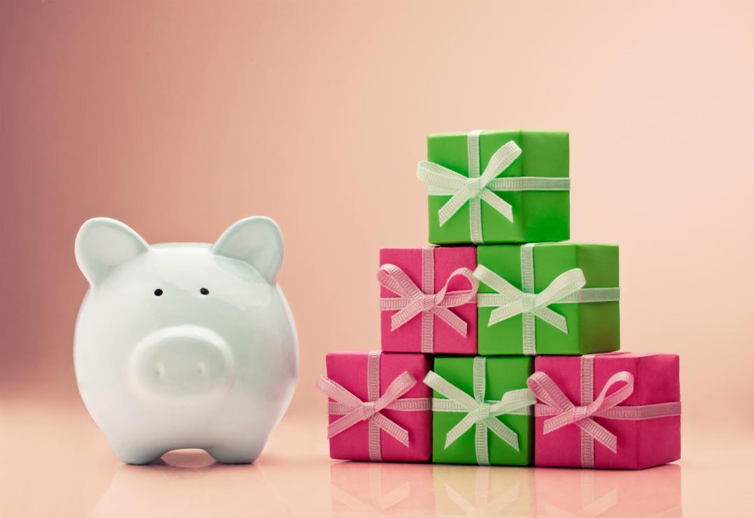 Коледни подаръци, натрупани на куп и касичка-прасе до тях
