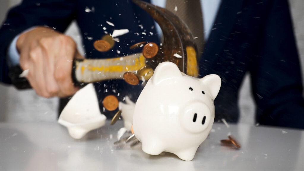 Човек, чупещ прасе-касичка, но все още нуждаещ се от спешни кредити онлайн